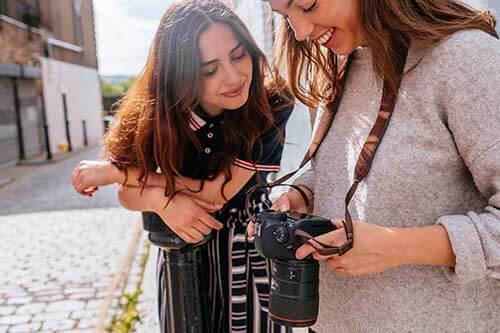 Zwei Fotografinnen schauen lächelnd auf das Display einer Canon Kamera