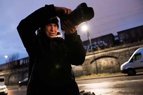 Fotograf fotografiert in der Stadt bei low light