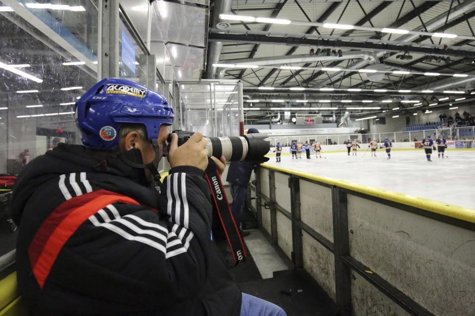 Mann fotografiert Eishockey mit Helm